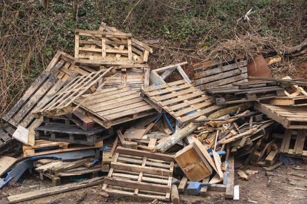 wooden pallets waste dumped on side of road